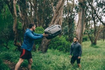 Zwei Männer in Wald werfen sich Travel Bag von Peak Design zu