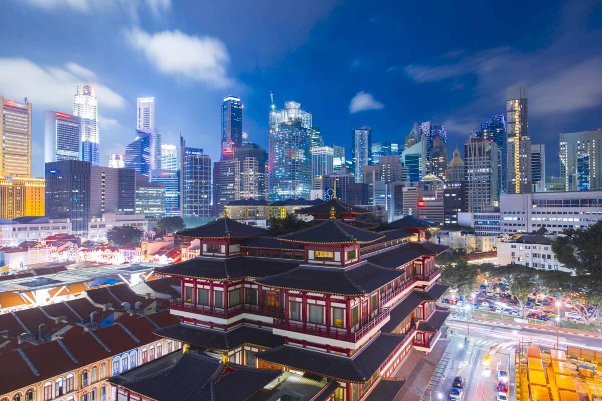 Belebtes Chinatown Viertel bei Nacht mit Skyline Singapurs im Hintergrund