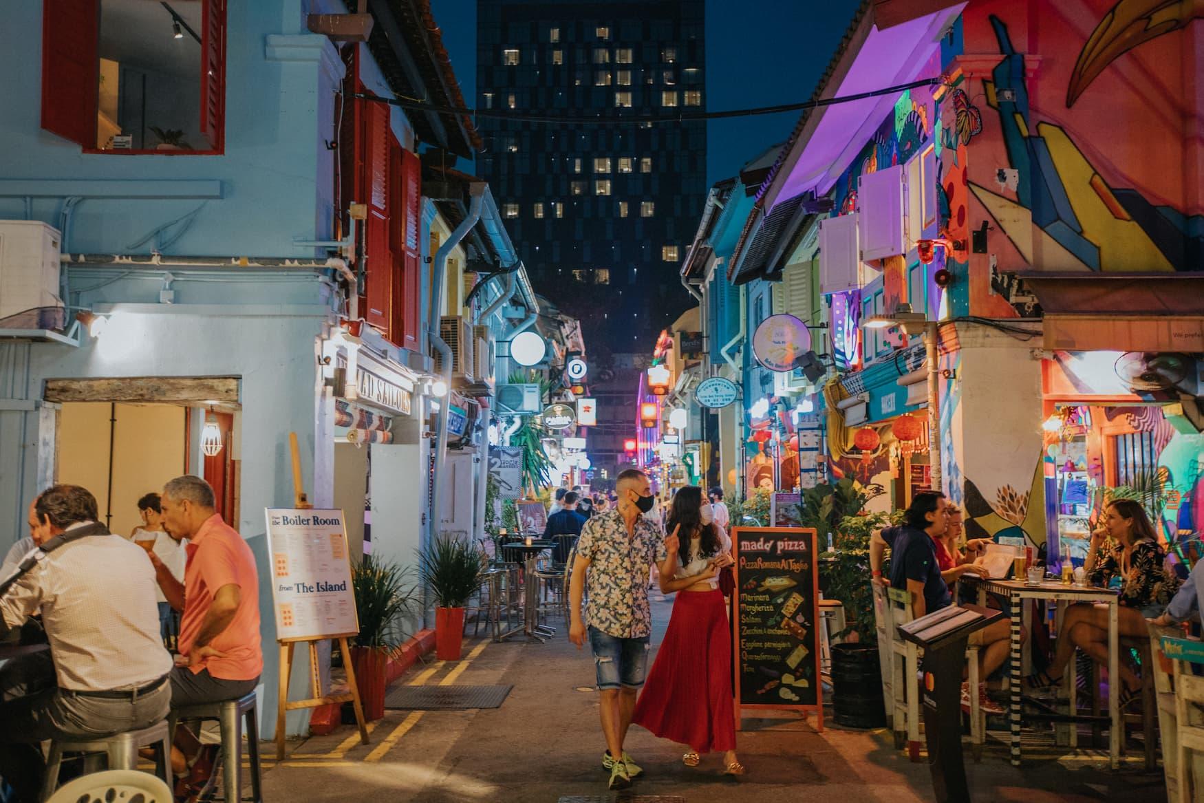 Menschen spazieren über die Haji Lane in Singapur und essen Streetfood