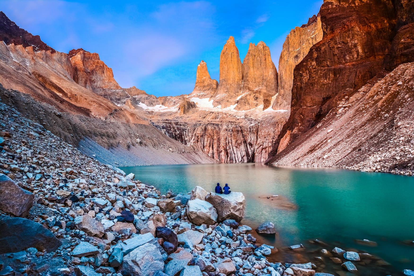 Menschen sitzen am Gletscher der Laguna Torre in Patagonien