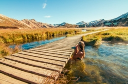 Frau badet in See im Landmannalaugar-Gebirge in Island