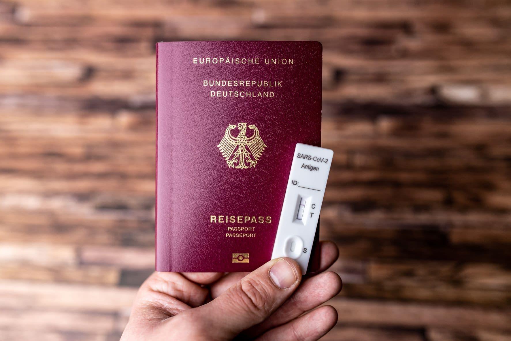 Person hält deutschen Reisepass und einen Corona-Antigen-Test in der Hand