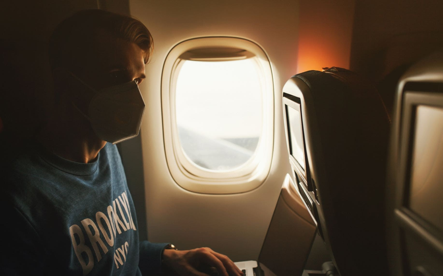 Junger Mann sitzt im Flugzeug und trägt einen Mund-Nasen-Schutz