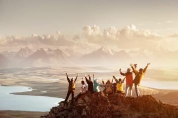 Gruppe von Leuten mit aufgewachsenen Armen auf einem Berggipfel
