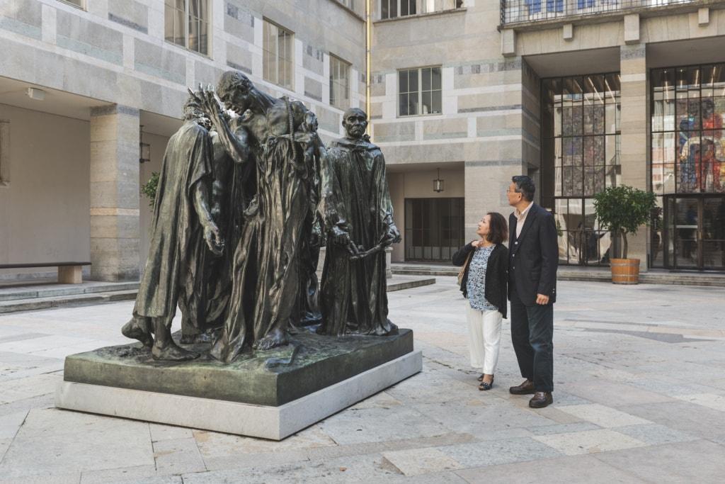 Paar betrachtet eine massive Statue vor dem Kunstmuseum in Basel, Schweiz.