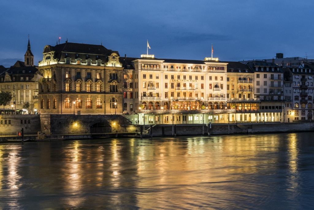 """Die Fassade des """"Grand Hotel Les Trois Rois"""" bei Nacht in Basel, Schweiz"""