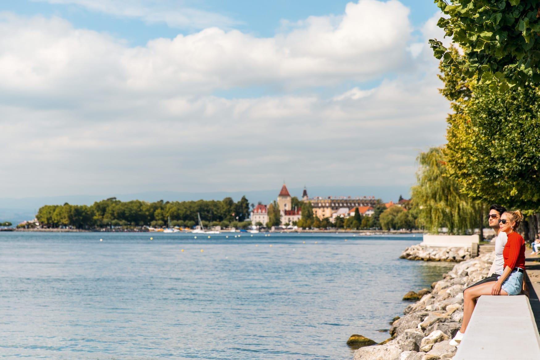 Junges Paar sitzt am Quai d'Ouchy Ufer, Lausanne, Schweiz.
