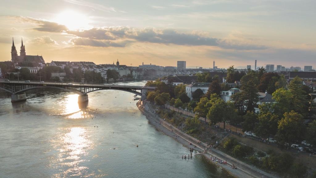 Drohnenaufnahme vom Rheinschwimmen und der Stadt Basel im Abendlicht