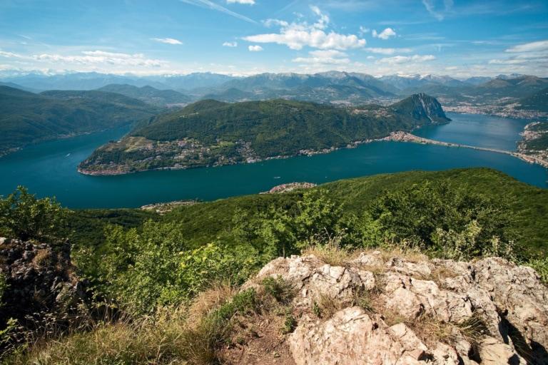 Auf dem Gipfel des Monte San Giorgio. Blick ueber den Lago di Lugano mit der Halbinsel Morcote und Monte San Salvatore