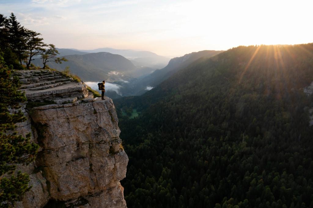 Sonnenaufgang am Creux du Van Neuchatel mit einem Mann, der auf einer steilen Klippe steht und dem warmen Sonnenlicht über dem Grat entgegensieht