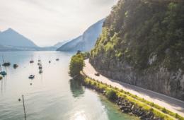 Roadtrip durch die Schweiz: Ein Mazda fährt entlang der Seestrasse am Thunersee, links der Niesen