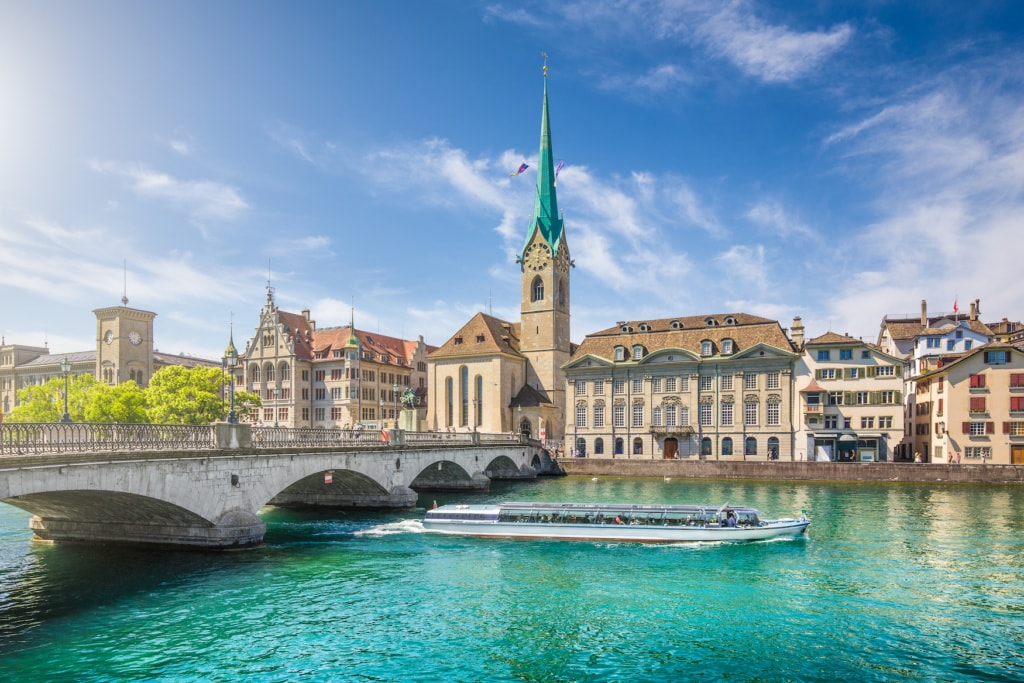 Schöne Aussicht auf das historische Stadtzentrum von Zürich mit der berühmten Fraumünsterkirche und Ausflugsboot auf der Limmat an einem sonnigen Tag mit blauem Himmel