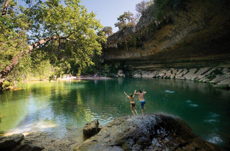 Zwei Personen springen in den Hamilton Pool in Texas