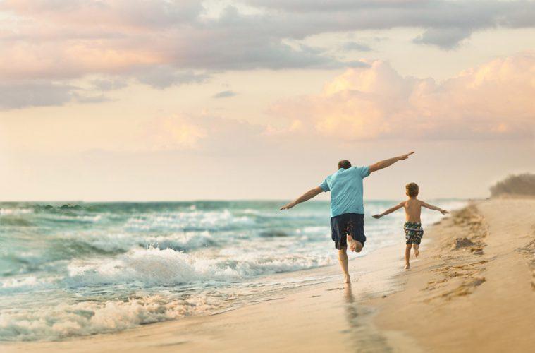 Ein Mann und Kind laufen am Strand in Fort Myers entlang