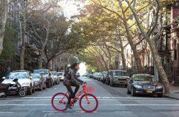 Ein Afroamerika fährt auf einem roten Fahrrad auf einer Straße in Brooklyn