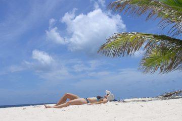 Frau im Bikini im Sand liegend auf Anguilla