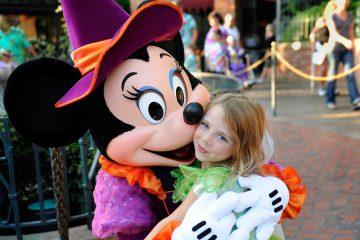 Ein Kind in den Armen von Mickey Mouse in einem der Freizeitparks in Orlando