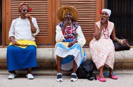 Drei Frauen sitzen auf einer Bank in Havanna