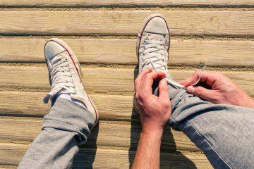Mann in Jogginhose schnürt sich seine Schuhe