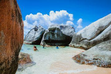 Badende in einer Strandbucht auf den Britischen Jungferninseln