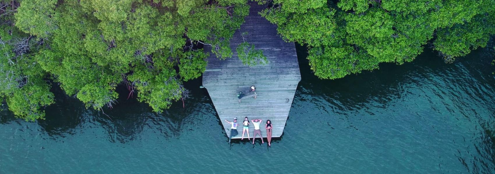 Junge Leute liegen auf Steg vor Mangrovenwäldern auf Tobago