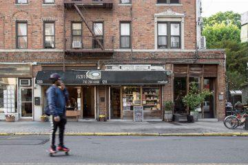Straßenszene in Brooklyn: Junger Afroamerikaner auf einem Skateboard fahrend