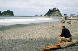 Ein Mann sitzt auf einem Baumstamm am Strand
